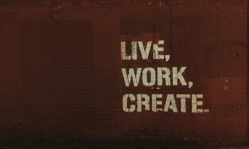 """A painted wall which reads """"Live, Work, Create"""", a central theme of the His and Her FI Post FI blog"""